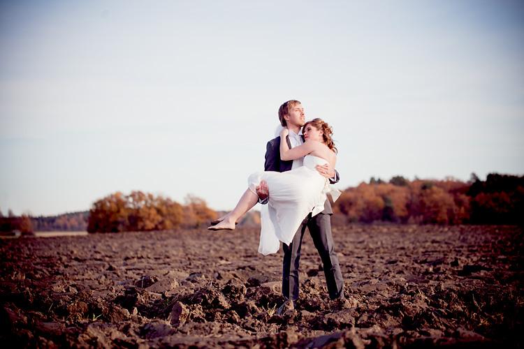 Brudpar på åker fotograferat av bröllopsfotograf Jessica Lund
