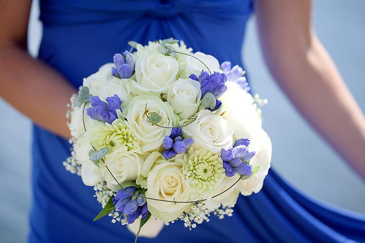 brudbukett med vita rosor och blå blommor