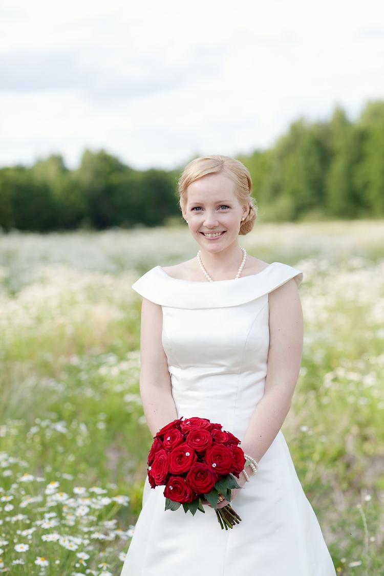 norsk brud i tubklänning med brudbukett röda rosor