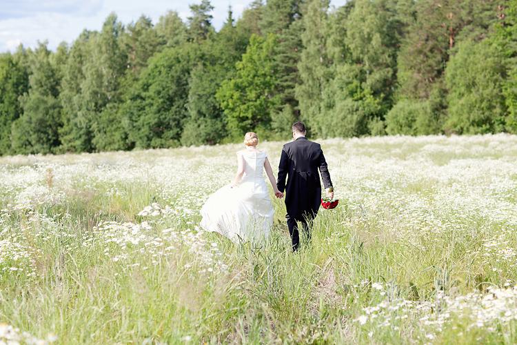 brudpar vandrar till sin bröllopsfest över äng