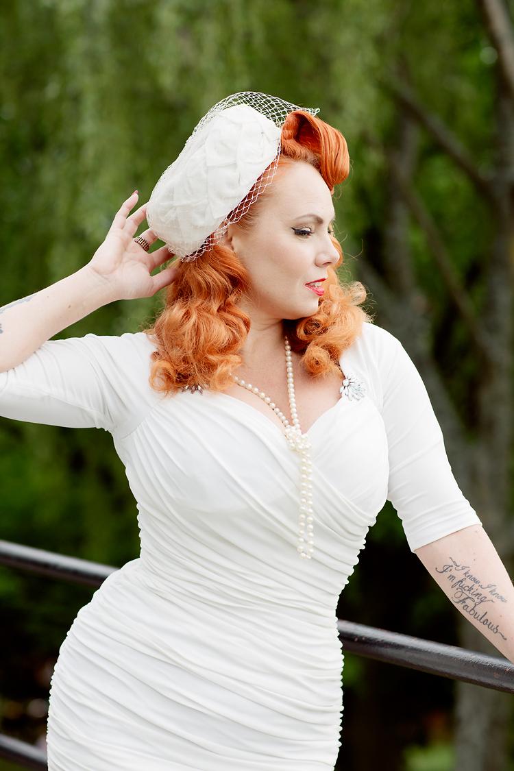 Mrs Murphy i vit klänning och hatt med flor