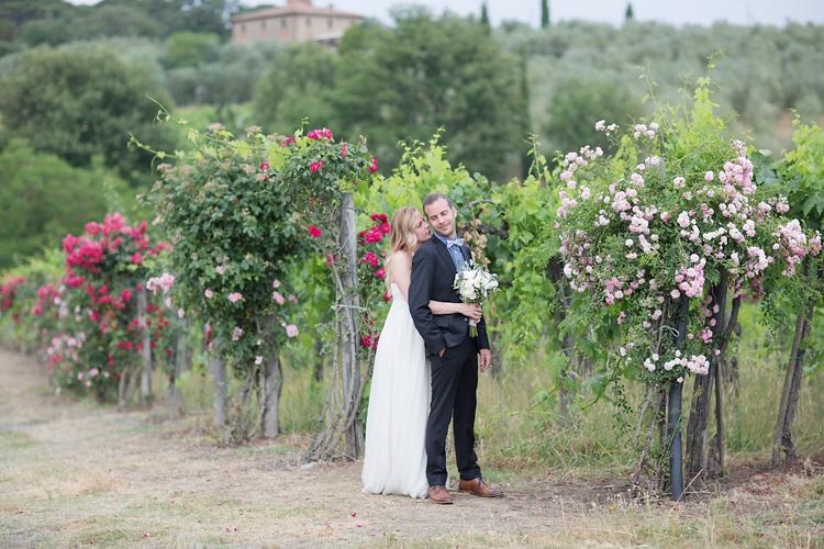 brudpar vid vinrankor med rosor