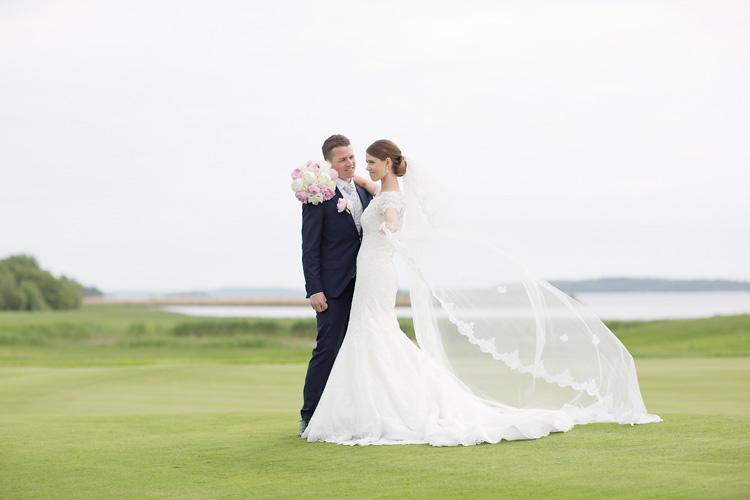 Bröllopsfotografering med lång slöja på golfbana