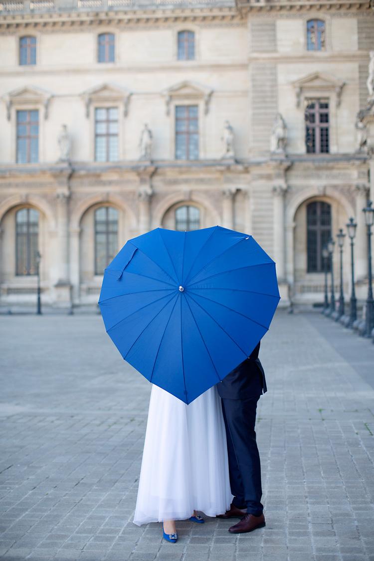 Blått paraply och brudpar